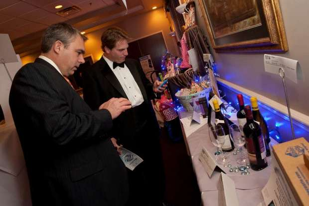 Two guests placing at a charity auction using OneCause's electronic bidding