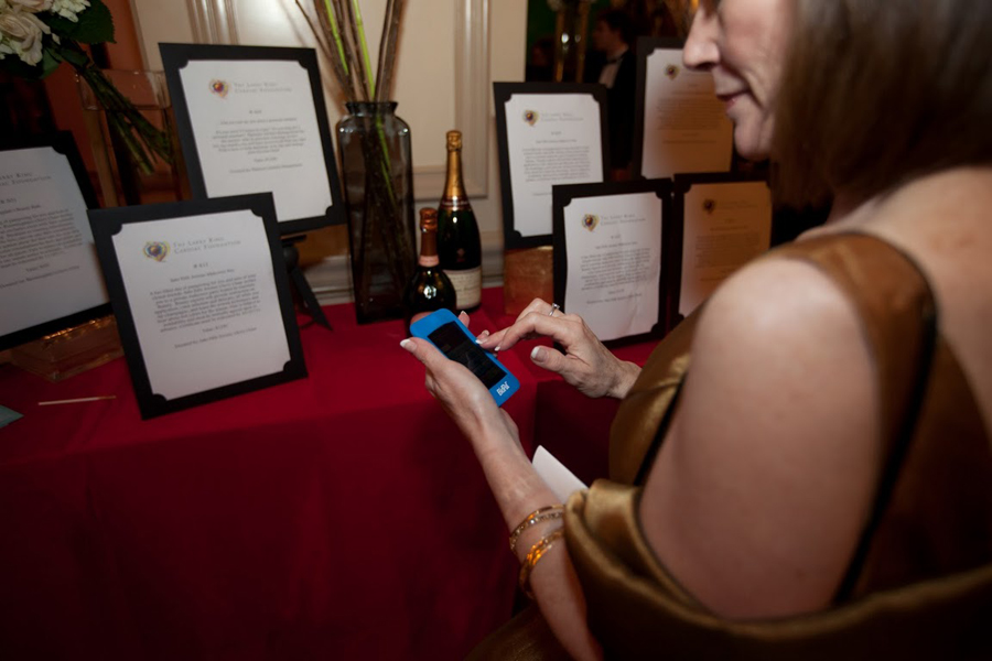 A guest at a charity fundraiser with a mobile device placing bids via OneCause's mobile bidding