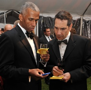 Two gentlemen using a mobile device to place bids on silent auction items via OneCause's fundraising software.