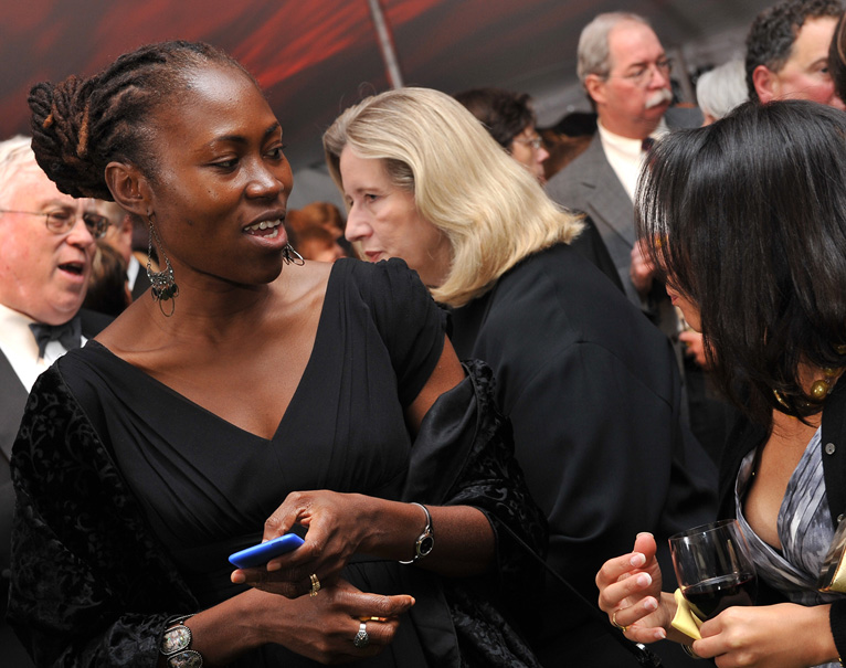 Two guests at a charity event, one of which is holding a mobile device running OneCause's mobile auction software