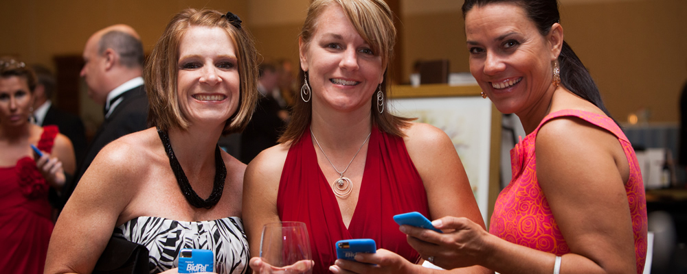Three smiling women holding mobile devices that are running OneCause's mobile auction software.