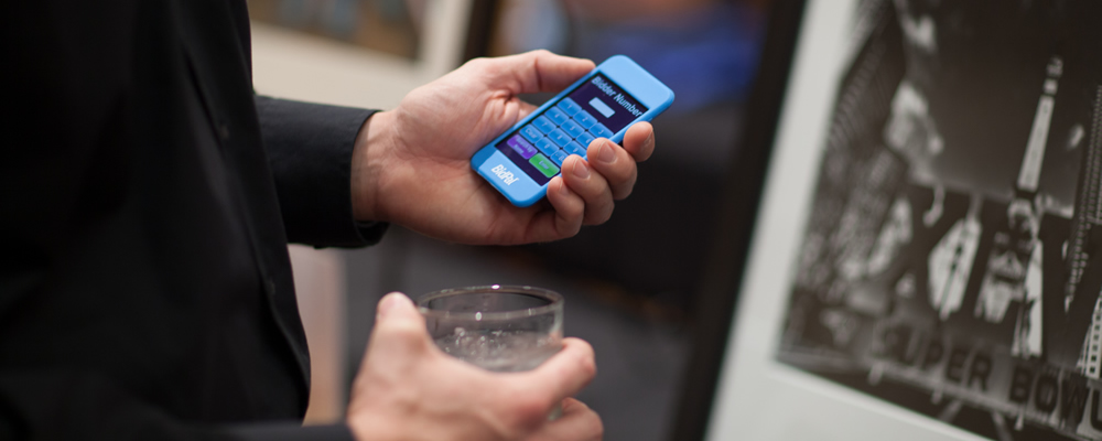 Guest holding a mobile device using OneCause's intuitive software at a charity fundraiser.