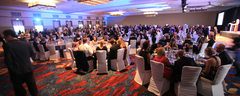 Guests seated in a ballroom using OneCause's mobile bidding to place bids on silent auction items.
