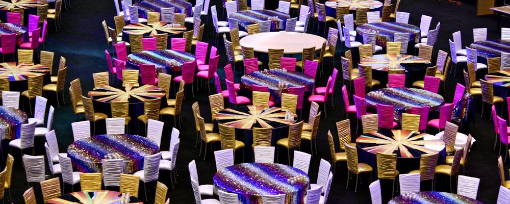 Photo of a ballroom with festive table cloths.
