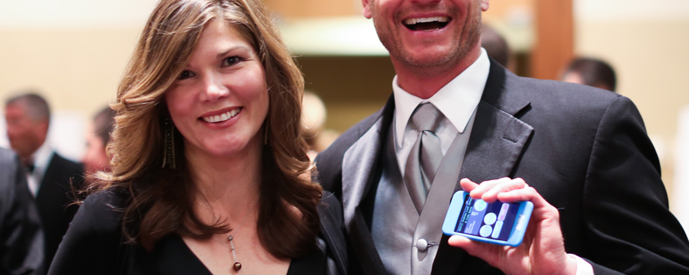 Two guests happy guests using OneCause's mobile bidding at an event.