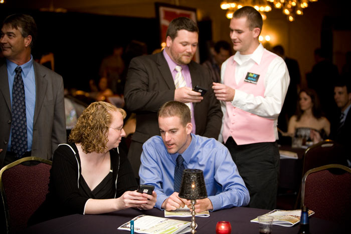 OneCause staff member Nathan Jeffery answering guest questions at a charity event utilizing OneCause mobile bidding.