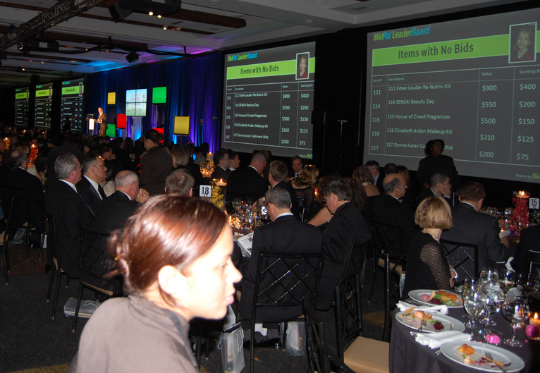 "Charity auction guests enjoying meal while watching OneCause's scoreboard technology display ""Items with No Bids"""