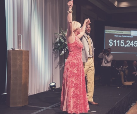 A Woman with her hands in the air celebrating at an event that achieved its fundraising goal by using mobile bidding